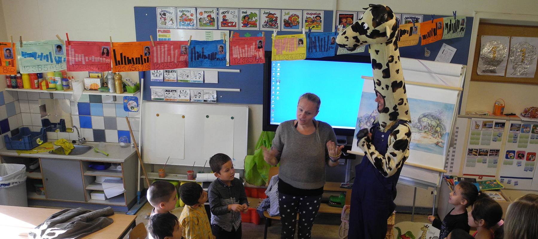 Giraf leert fietsen op schoolbezoek