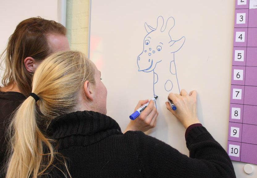 Marie-Louise en Mark tekenen samen tijdens een schoolbezoek