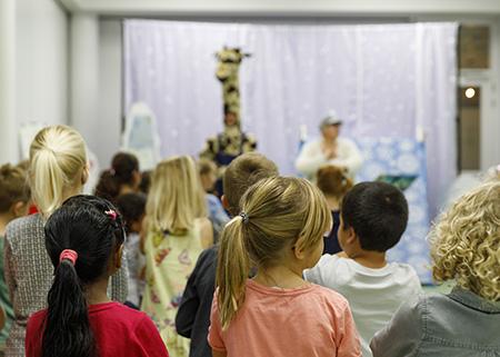 kinderen kijken naar de voorstelling van giraf en zebra